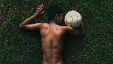 topless man lying on green grass field