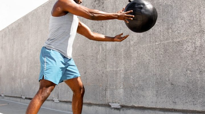 man in white tank top and white shorts holding black ball